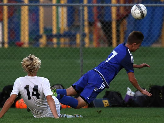 Blake Wilcox trips up Tom Harenda during a game against Waukesha West at Kettle Moraine High School Tuesday, Sept. 20, 2016.