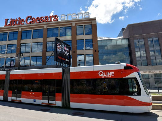 A QLine Detroit streetcar departs the Sproat Street station as the car passes Little Caesars Arena.