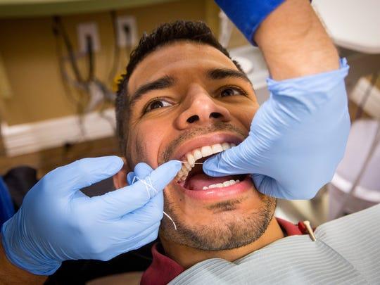 Dr. Mathew Petersen, doctor of dental surgery, flosses