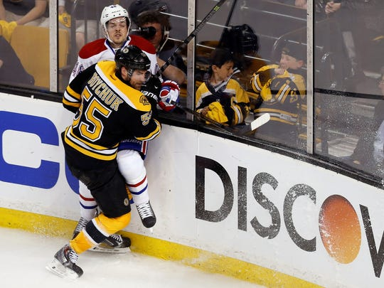 May 1, 2014: Boston Bruins defenseman Johnny Boychuk (55) checks Montreal Canadiens center Daniel Briere (48) into the glass during the first overtime period in game one of the second round of the 2014 Stanley Cup Playoffs at TD Banknorth Garden.
