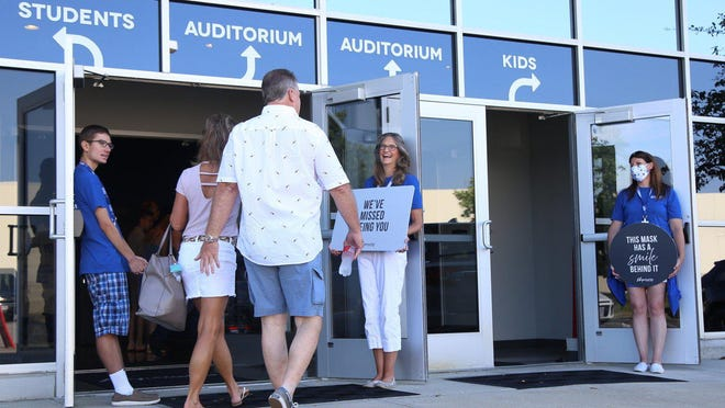 Lifepoint Christian Church volunteers Brandon March, Denise Tidwell, and Jen Taylor, wearing blue shirts, hold signs welcoming worshipers while holding doors open before the 9:30 a.m. service at the Lewis Center campus on Sunday.
