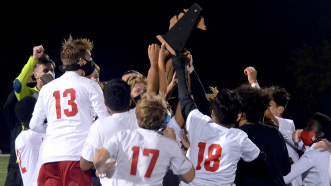 The Holland boys soccer team celebrates winning the Division 2 district title on Thursday at Holland Christian.