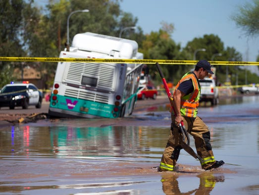 A Tempe firefighter works the scene of a water main break at the intersection of McClintock and Apache in Tempe on Wednesday, Sept. 3, 2014. A Valley Metro bus was also stuck in a hole.