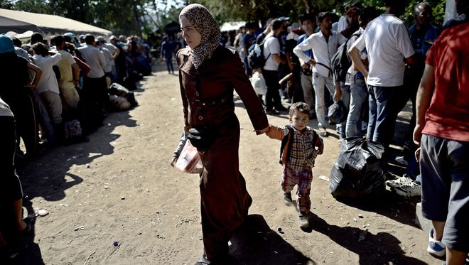 A mother holding her child walks at a registration camp in Presevo as Syrian refugees and migrants arrived in Serbia on Aug. 30, 2015. The EU is grappling with an unprecedented influx of people fleeing war, repression and poverty in what the bloc has described as its worst refugee crisis in 50 years.