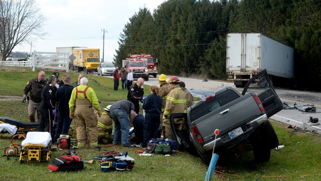 First responders treat an injured driver after an accident between a pickup and a semi tractor-trailer Wednesday, Dec. 16, 2015, on U.S. 35 north of Centerville Road and Williamsburg.