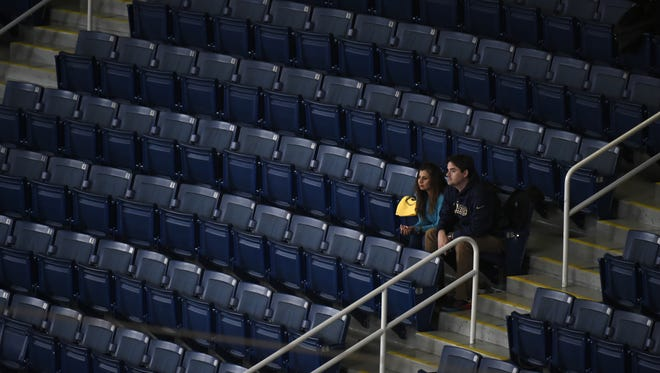 A few fans are surrounded by empty seats inside Edward Jones Dome as the St. Louis Rams played what could have been their final home game in St. Louis.