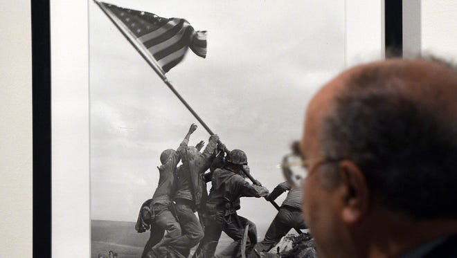 "A visitor looks at Joe Rosenthal's ""Raising the Flag on Iwo Jima"" 1945 during the 'Life. I grandi fotografi""  exhibition at the auditorium on April 30, 2013 in Rome."