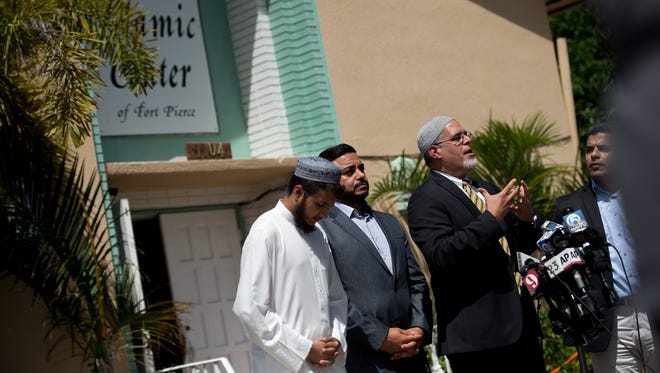 Wilfredo Ruiz (right), communications director for the Council on American-Islamic Relations in Florida, talks with news media outside the Islamic Center of Fort Pierce on Monday, Sept. 12, 2016, where officials said a fire was set by an arsonist at 12:40 a.m. Assistant Imam Syed Hamaad Ur Rahman (left) and United Voices for America President Ahmed Bedier (center) also spoke.