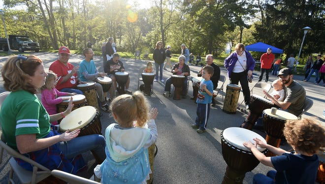 Kids and adults create music in a drum circle in Glen Miller Park in 2016.