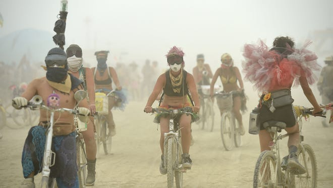 Burners ride through the streets of Black Rock City during a dust storm at Burning Man. Mandatory Credit: