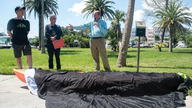 """""""It's not only an environmental disaster, it's an economic disaster,"""" said Stuart city commissioner Troy McDonald (right), who stood next to local business owner Sebastian LaHara (left) and his customer and friend Sam Yates, of Jensen Beach, at a kayak funeral to memorialize the end of LaHara's kayak and paddle board sales, on Tuesday, July 3, 2018 at Shephard Park in Stuart. Because of polluted water, LaHara will be closing the Triathletica Sports/Riverfront Kayaks business next to Frazier Creek, rebranding as Bikes Plus and relocating to two new locations in Stuart and Palm City. """"It's unfortunate and very hard,"""" LaHara said at the news conference. """"Every year it has been declining."""""""