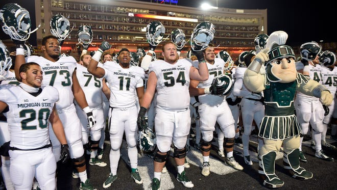 Michigan State's Connor Kruse (54), Dennis Finley (73), Jamal Lyles (11), Nick Hill (20) and others celebrate a 37-15 win over Maryland in an NCAA college football game, Saturday, Nov. 15, 2014, in College Park, Md.