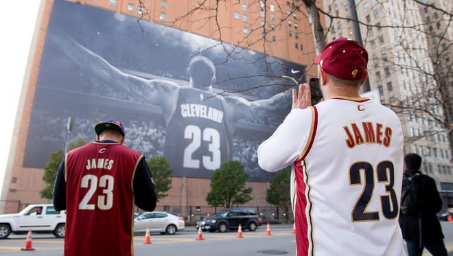 Fans take pictures of a mural of LeBron James in Cleveland near Quicken Loans Arena.