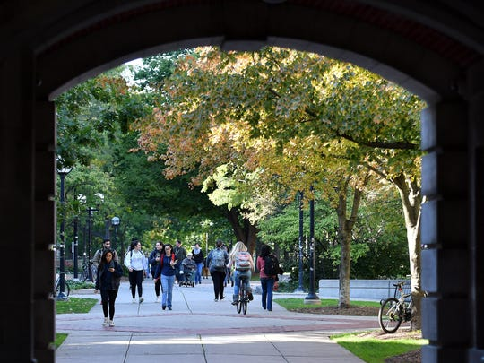 People move through the Diag on the campus of the University of Michigan in Ann Arbor, Mich. on Oct. 17, 2017.