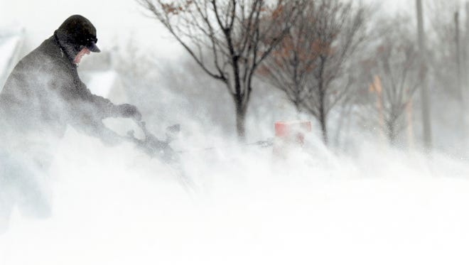 Gary Quamme fights through the snow flying back in his face as he blows snow in Bismarck, N.D.,  on Dec. 4.