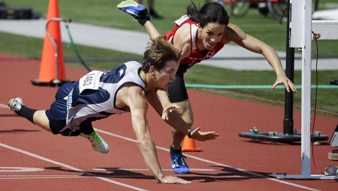 Xavier's Nathan Broullire, left, falls across the finish line ahead of Shorewood's Edgardo Valdes after the two collided Saturday in the 800-meter run at the WIAA Division 2 state track meet in La Crosse.