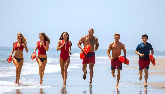 """This image released by Paramount Pictures shows, from left, Kelly Rohrbach as CJ Parker, Alexandra Daddario as Summer, Ilfenesh Hadera as Stephanie Holden, Dwayne Johnson as Mitch Buchannon, Zac Efron as Matt Brody and Jon Bass as Ronnie in the film, """"Baywatch."""" ("""