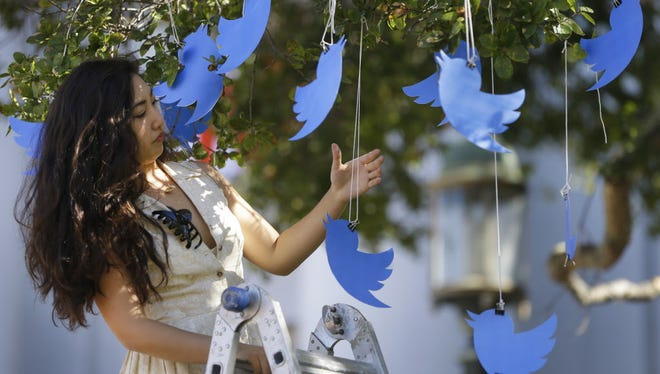 Karen Kim hangs Twitter icons in a commemoration of the 1964 Free Speech Movement at UC-Berkeley.