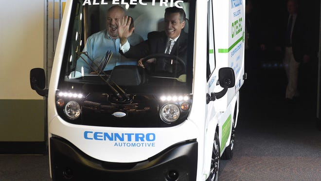 Gov. Brian Sandoval, right, accompanied by Sparks Mayor Geno Martini arrive at a press conference in a Cenntro electric vehicle Friday morning at the Reno-Sparks Convention Center. The Economic Development Authority of Western Nevada announced the arrival of Benntro, which will built electric utility vehicles and scooters in Sparks, bringing an estimated 300 new jobs to the area.