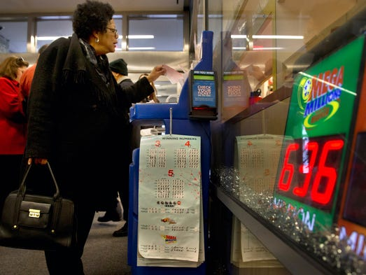 A woman fills out her Mega Millions ticket at The Gallery Shop on Dec. 17 in Washington. The Mega Millions jackpot has soared to $636 million, making it the second largest lottery jackpot in U.S. history.