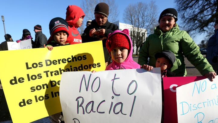 From left, Reyle Flores, 7, Ivan Vallejo, 11, Efren Flores, Xitlaly Flores, 6, Yair Flores, 4, and Isabel Vallejo, all of Woodburn, carry signs during an immigrant rights rally at the Oregon State Capitol in Salem on Saturday, Jan. 14, 2017.