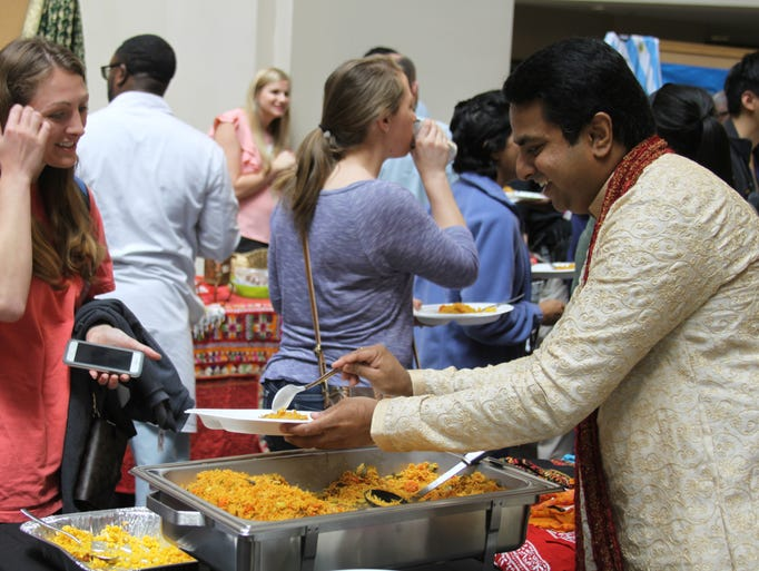 Dr. Harish Siddaiah serves food to students at the