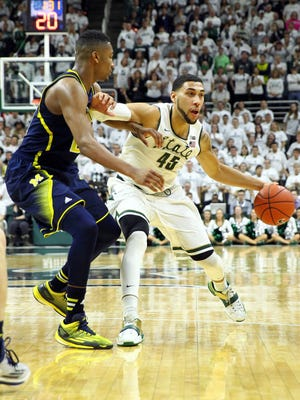 Michigan State  guard Denzel Valentine dribbles the ball around Michigan Wolverines forward Aubrey Dawkins during the second half at Jack Breslin Student Events Center. The Spartans won 76-66.