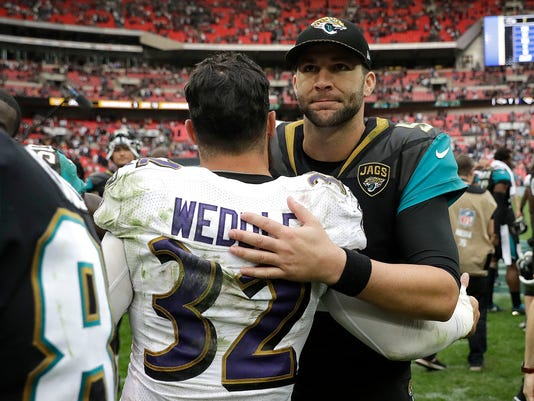 Jacksonville Jaguars quarterback Blake Bortles, right, greets Baltimore Ravens free safety Eric Weddle after an NFL football game at Wembley Stadium in London, Sunday Sept. 24, 2017. The Jaguars won 44-7. (AP Photo/Matt Dunham)