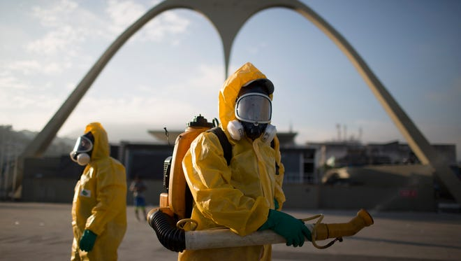 Health workers, in this January,2016 photo, stand in the Sambadrome spraying insecticide to combat the Aedes aegypti mosquito that transmits the Zika virus in Rio de Janeiro. The Sambadrome will be used for the Archery competition during the 2016 summer games.