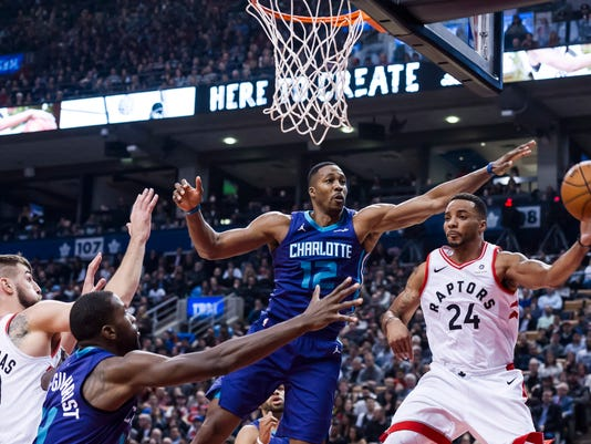 Toronto Raptors forward Norman Powell (24) looks to pass under the net under pressure from Charlotte Hornets' Dwight Howard (12) during the first half of an NBA basketball game Wednesday, Nov. 29, 2017, in Toronto. (Christopher Katsarov/The Canadian Press via AP)