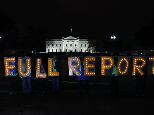 "Members of the protest group Herndon Reston Indivisible and Kremlin Annex hold signs saying ""Full Report,"" outside the White House in Washington, Monday, March 25, 2019, as they protested for the complete results to be released of special counsel Robert Mueller's investigation into Russian election interference and possible coordination with associates of President Donald Trump."