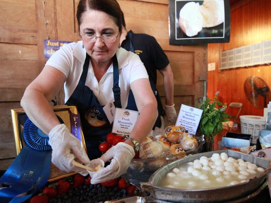 Pattie Federica, of Naragansett Creamery hands out samples of fresh cheese during the Vermont Cheesemakers' Festival at Shelburne Farms in Shelburne, VT on Sunday, July 24, 2011. (Joshua Lambert, for the Free Press)