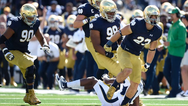 Fighting Irish safety Drue Tranquill (23) on Sept. 19, 2015, celebrates his tackle of  Georgia Tech Yellow Jackets running back Qua Searcy (1) for a loss in the first quarter at Notre Dame Stadium.