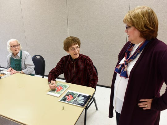St. Cloud Aging Services Director Kim Hood talks with participants in a painting class Tuesday, Oct. 25, at the Whitney Senior Center in St. Cloud.