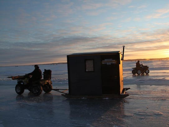 Sturgeon spearers use ATVs to position spearing shacks