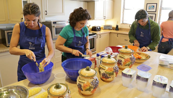 L-R, Laurie Motola, Susan Garcia and Joseph Reyes, chop and prepare veggies for soup. They are members of the Soup Troop, who makes soup for Hospice patients, as seen in Phoenix, on Sept. 23, 2014.