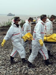 Rescue workers carry a body recovered from a capsized