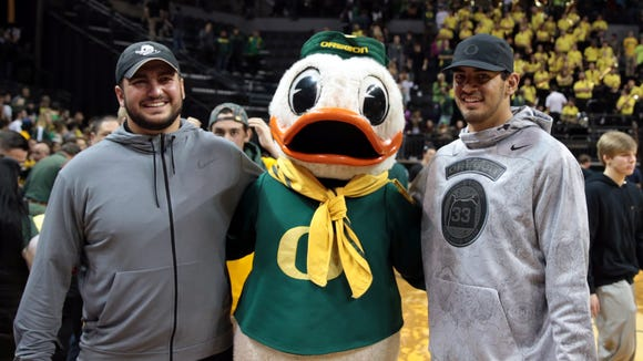 Jan 23, 2016; Eugene, OR, USA; Oregon Ducks mascot stand with Tennessee Titans quarterback Marcus Mariota and Chicago Bears Center Hroniss Grasu at the end of the game against the UCLA Bruins at Matthew Knight Arena. Mandatory Credit: Scott Olmos-USA TODAY Sports