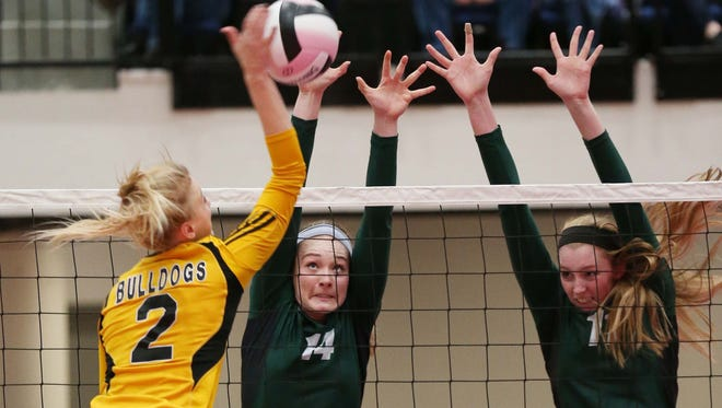 Bettendorf's Josie Herbst tries to drive the ball past Iowa City West's Laynie Whitehead (14) and Emily Halverson (11) during the 2014 Class 5A State Volleyball Tournament in Cedar Rapids, Iowa, Tuesday Nov. 11, 2014.
