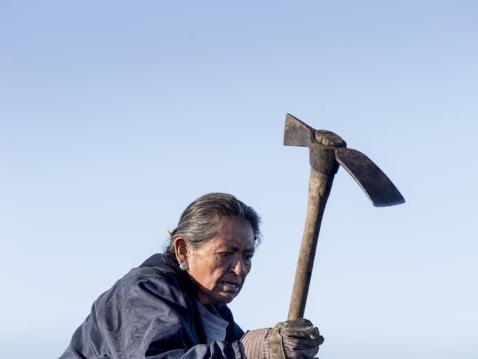 Charlotte Begay, 64, of Shonto, Ariz., breaks up coal