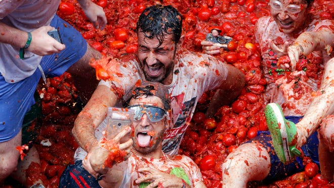 """Revelers take pictures as they enjoy throwing tomatoes at each other, during the annual """"Tomatina"""", tomato fight fiesta."""