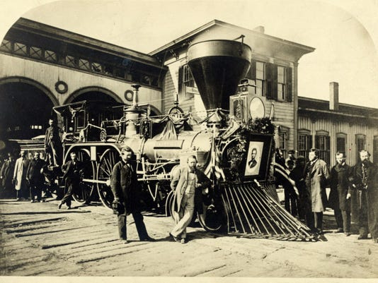 This photo shows a Cleveland, Columbus & Cincinnati Railroad engine, with a portrait of Abraham Lincoln mounted on the front. The engine was one of several used to carry Lincoln's body from Washington, D.C., to Springfield, Ill.