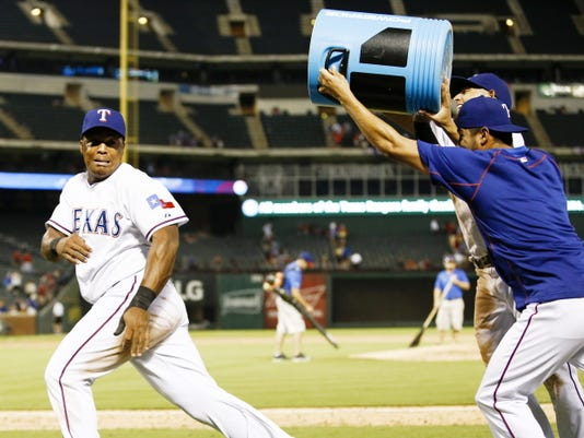 Texas Rangers' Adrian Beltre, left, is chased by Rougned Odor, right rear, and Martin Perez, right, with a water cooler following the Rangers 12-9 win over the Houston Astros during a baseball game, Monday, Aug. 3, 2015, in Arlington, Texas. Beltre hit for the cycle during the game. (AP Photo/Jim Cowsert)