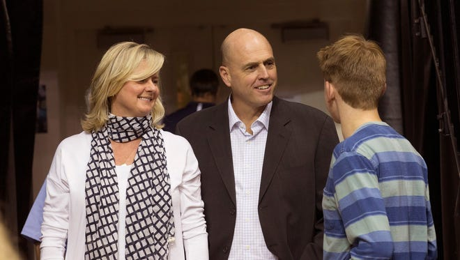 Dave Calloway (center), a former Monmouth University men's basketball player and coach, stands with his wife, Denise, and son, Dave, at OceanFirst Bank Center on  Friday night.