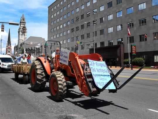 Tom John drives tractor pulling a hay wagon and protestors