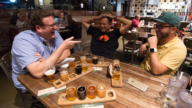 News Journal reporter Ryan Cormier, left, Dogfish founder Sam Calagione (center) and Dogfish head brewmaster Bryan Selders talk at Dogfish Head Brewings & Eats in Rehoboth Beach on Tuesday night.