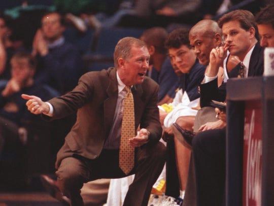Michigan coach Steve Fisher talks to Jalen Rose on