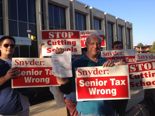 Protesters gather outside an appearance by Gov. Rick Snyder in Kalamazoo Monday, Sept, 29, 2014.