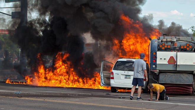 A bystander stands next to the driver of the minivan as both vehicles are engulfed in flames after a fatal accident near 32nd Street and Broadway Road on Aug. 20, 2017.