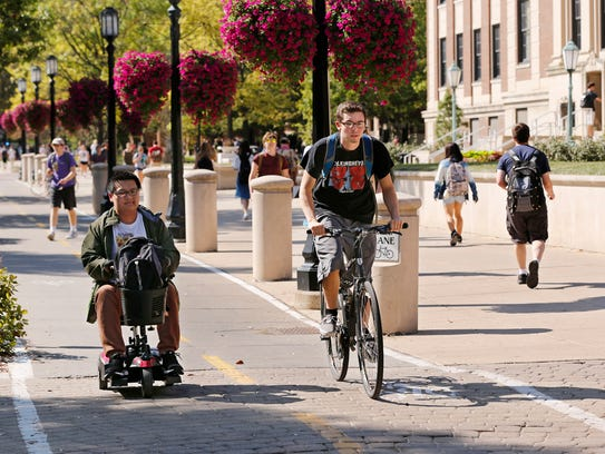 A student pedals along the bike lane in front of Wetherill